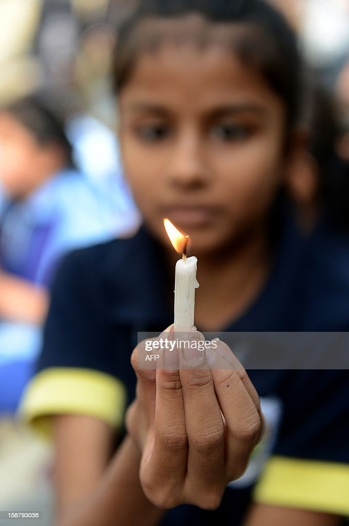 Indian schoolgirl holds a candle during a rally in Ahmedabad on December 29, 2012, after the death of a gangrape victim from the Indian capital New Delhi. Indian leaders appealed for calm and security forces headed off fresh unrest by turning New Delhi into a fortress after a student who was savagely gang-raped died in a Singapore hospital. Police threw a ring of steel around the centre of the Indian capital after news of the 23-year-old medical student's death was broken in the early hours by the Singapore hospital that had been treating her for the last two days. AFP PHOTO/Sam PANTHAKY