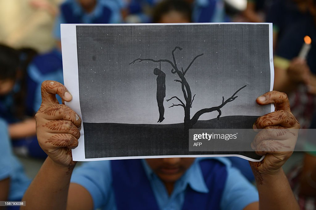 Indian schoolgirl holds a placard with an image of a hanging man during a rally in Ahmedabad on December 29, 2012, after the death of a gangrape victim from the Indian capital New Delhi. Indian leaders appealed for calm and security forces headed off fresh unrest by turning New Delhi into a fortress after a student who was savagely gang-raped died in a Singapore hospital. Police threw a ring of steel around the centre of the Indian capital after news of the 23-year-old medical student's death was broken in the early hours by the Singapore hospital that had been treating her for the last two days.
