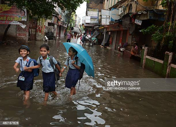 Indian schoolgirls walk along a waterlogged street following heavy rain in Kolkata on July 10 2015 AFP PHOTO/ Dibyangshu Sarkar