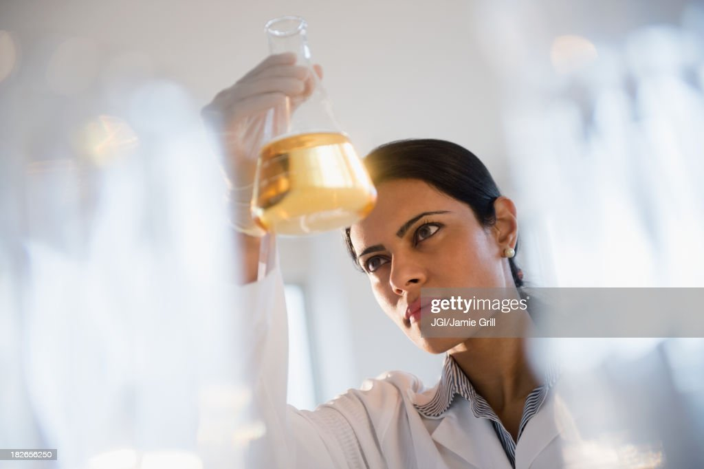 Indian scientist examining chemicals in lab : Stock Photo