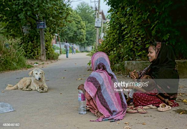 Indian scrap seller women gestures towards a stray dog as they rest on a road while enjoying some relief from scalding temperatures on August 11 2015...