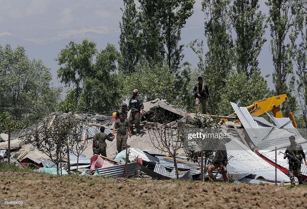 Indian security forces search a destroyed house after a gunbattle between militants and Indian soldiers in Kotchipora village near Tangmarg in north Kashmir's Baramulla district on May 27, 2016. Indian troops shot dead two suspected militants and destroyed one house during the gunbattle. Six suspected rebels and a soldier died in two separate gun battles in Indian Kashmir as violence flared in the restive region this week, police and the army said May 27. / AFP / STR