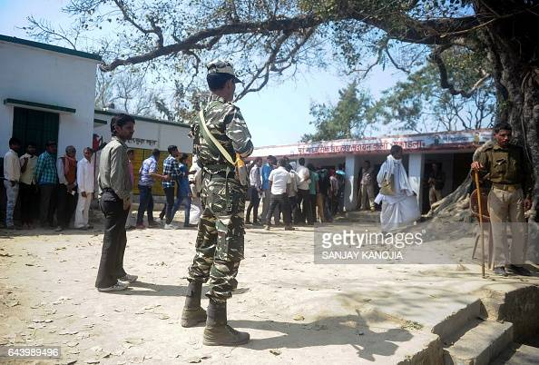 Indian security forces stand guard as voters wait in a queue for their turn to vote at a polling station in the Naini area on the outskirts of...