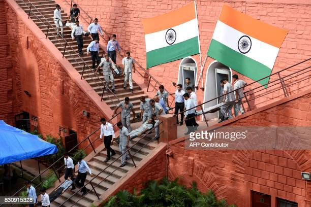 Indian security forces take part in a mock drill during the fulldress rehearsal for the 71st Independence Day celebrations at the Red Fort in New...