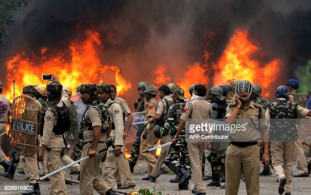 Indian security forces walk next to burning vehicles set alight by rioting followers of a religious leader convicted of rape in Panchkula on August...
