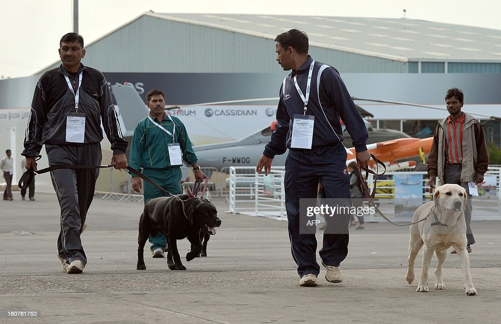 Indian security officials walk with sniffer dogs near aircraft on display for the 9th edition of Aero India 2013 at the Yelahanka Air Force station in Bangalore on February 5, 2013. The 5-day event starting from January 6 will be inaugurated by Indian defence minister AK Antony and is a major platform for foreign vendors. The biennial event is crucial to international participants and investors at a time when the Indian government is set to spend USD 100 billion in the defence sector within the next five years. AFP PHOTO/ Manjunath KIRAN