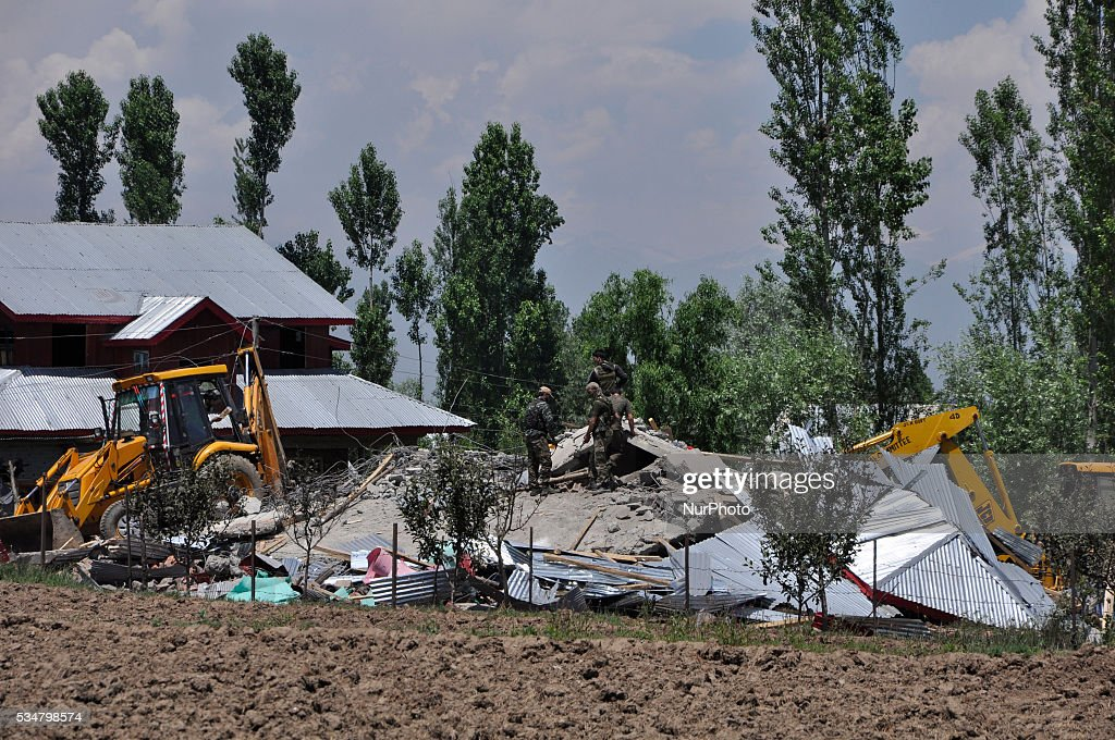 Indian security personal walk past the debris of the damaged residential house in which the two rebels were holed up in Khonshipora 25 miles west of srinagar on May 27,2016.Two rebels were killed by indian forces during a brief gunfight.