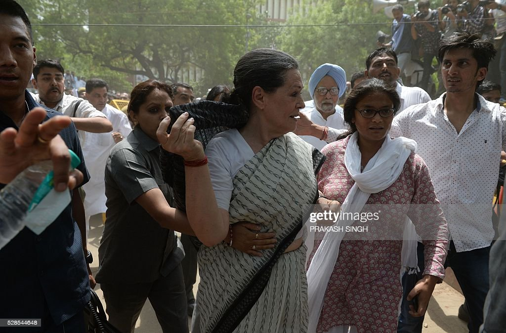 Indian security personnel escort Congress Party President Sonia Gandhi (C) during the 'March for Democracy' protest against the National Democratic Alliance (NDA) government led by the Bharatiya Janata Part's (BJP) Narendra Modi in New Delhi on May 6, 2016. Former Indian prime minister Manmohan Singh, Congress Party President Sonia Gandhi and party Vice-president Rahul Gandhi were briefly arrested at a police station and later released during a 'Save Democracy' protest march against the ruling Bharatiya Janata Party (BJP). / AFP / PRAKASH
