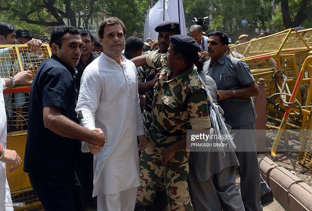 Indian security personnel escort Congress Party Vice President Rahul Gandhi (C) during the 'March for Democracy' protest against the National Democratic Alliance (NDA) government led by the Bharatiya Janata Part's (BJP) Narendra Modi in New Delhi on May 6, 2016. Former Indian prime minister Manmohan Singh, Congress Party President Sonia Gandhi and party Vice-president Rahul Gandhi were briefly arrested at a police station and later released during a 'Save Democracy' protest march against the ruling Bharatiya Janata Party (BJP). / AFP / PRAKASH