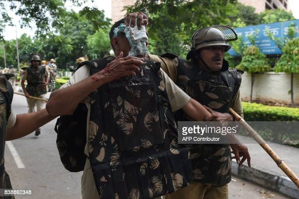 Indian security personnel help an injured colleague during clashes between the controversial guru's followers and security forces in Panchkula on...