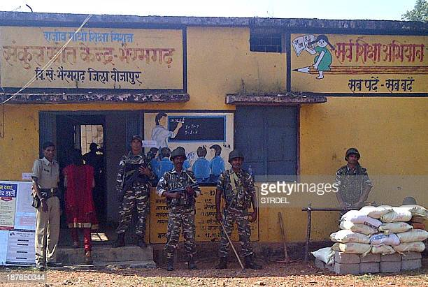 Indian security personnel keep watch at a polling station in Bhairamgarh Bijapur district in the Bastar region of Chhattisgarh on November 11 2013...