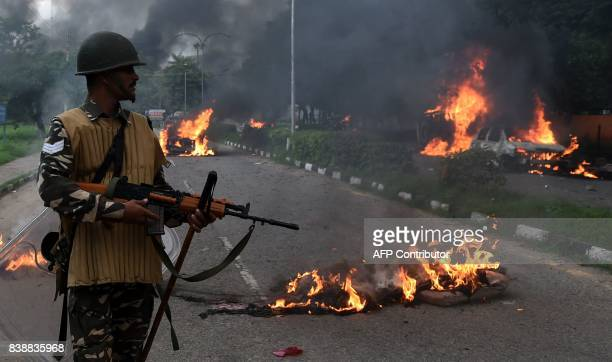 TOPSHOT Indian security personnel looks at burning vehicles set alight by rioting followers of a religious leader convicted of rape in Panchkula on...