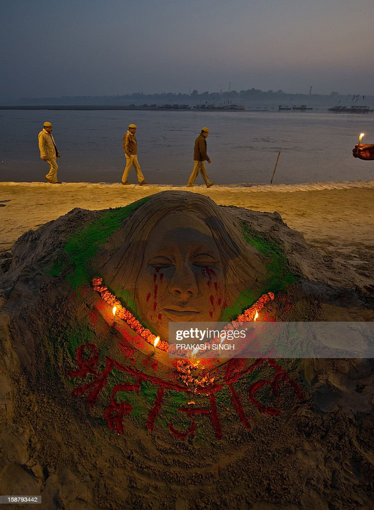 Indian security personnel pass by a sand sculpture by artist Raj Kapoor at Sangam in Allahabad on December 29, 2012, after the death of a gangrape victim from the Indian capital New Delhi. Indian leaders appealed for calm and security forces headed off fresh unrest by turning New Delhi into a fortress after a student who was savagely gang-raped died in a Singapore hospital. Police threw a ring of steel around the centre of the Indian capital after news of the 23-year-old medical student's death was broken in the early hours by the Singapore hospital that had been treating her for the last two days. AFP PHOTO/Prakash SINGH