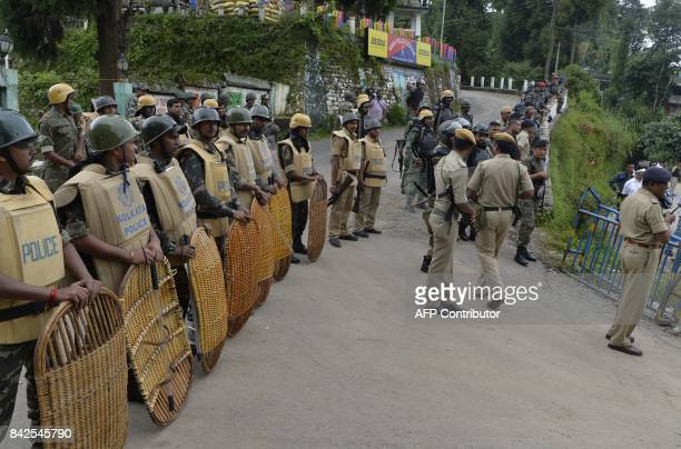 Indian security personnel stand guard as supporters of the Trinamul Congress along with local residents of Mirik take part in a rally urging a return...