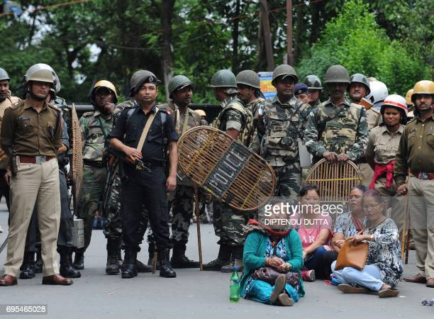 TOPSHOT Indian security personnel stand guard during a protest by supporters of the Gorkha Janmukti Morcha amid a general strike called by the GJM in...