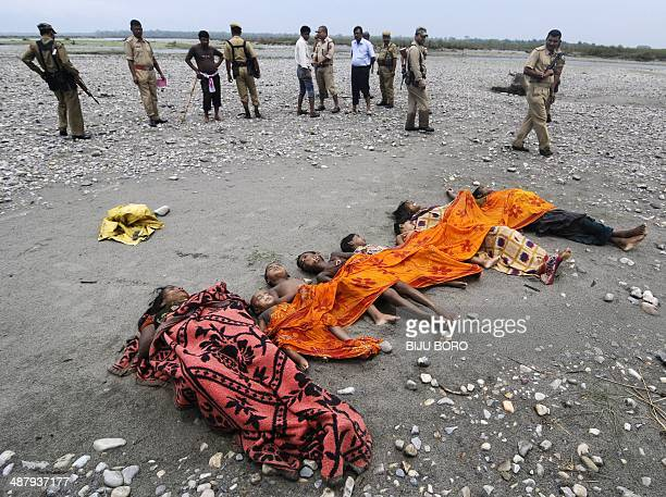 Indian security personnel stand near bodies lying on the banks of the River Beki in the village of Khagrabari some 200kms west of Guwahati on May 3...