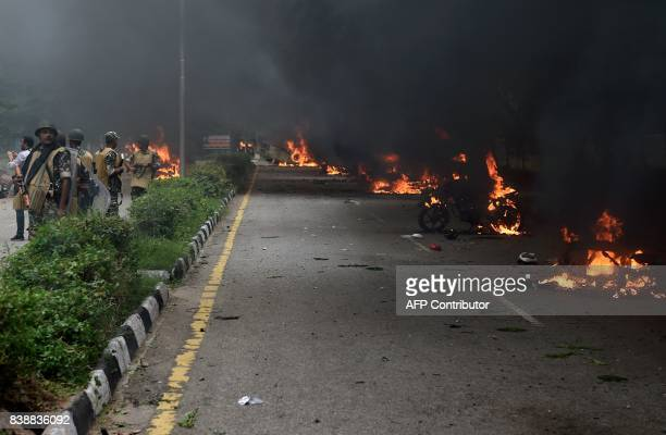 Indian security personnel stand near burning vehicles set alight by rioting followers of a religious leader convicted of rape in Panchkula on August...