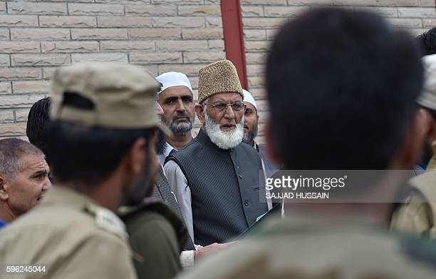 Indian security personnel stand near the chairman of the All Parties Hurriyat Conference Syed Ali Geelani who was detained as he tried to march...