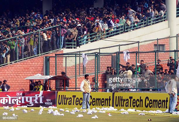 Indian security personnel stand on a pitch littered with debris thrown by angry supporters after the cancellation of the fifth and final One Day...