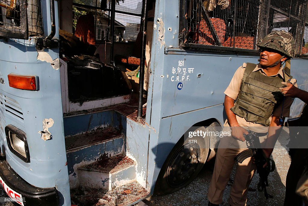 A Indian security personnel stands nex to a bus that had been carrying paramilitary troopers when it was attacked by suspected militants in Pampore, south of Srinagar, on June 25, 2016. At least eight Indian paramilitary soldiers and two suspected rebels were killed on June 25 near Srinagar in India-administered Kashmir when a group of armed militants ambushed the soldiers' convoy, police said. / AFP / STR