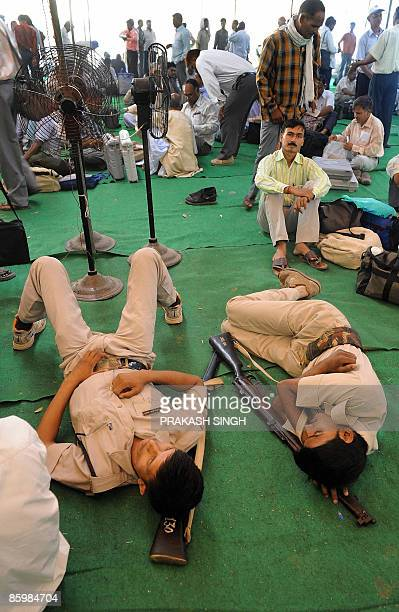 Indian security personnel take rest as polling officers check the workings of the Electronic Voting Machines after receipt from a distribution centre...