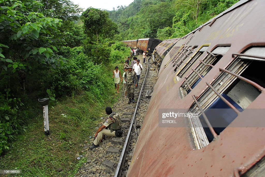 Indian security personnel walk past derailed compartments of the Barak Valley Express train, caused by a blast by suspected militants, near Halflong Railway Station, some 310 kms from Guwahati on October 27, 2010. Ten people were injured in the incident.