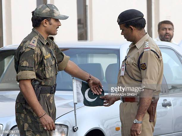 Indian security personnelS arrange Pakistan's national flag on the car of Pakistan's High Commissionner to India Aziz Ahmed Khan during the arrival...
