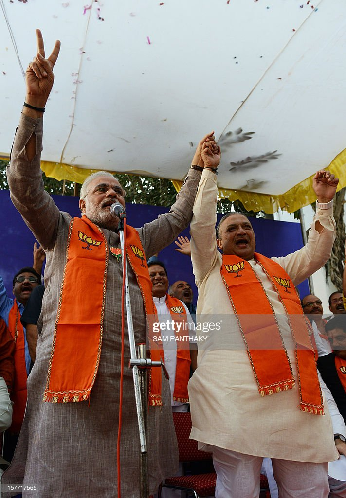 Indian senior Congress party leader and former Deputy Chief Minister of Gujarat state, Narhari Amin (R), raises his hands after being inducted in the Bhartiya Janta Party (BJP) by the Gujarat state Chief Minister - Narendra Modi (L) in Ahmedabad on December 6, 2012. Amin resigned from the Congress Party two days ago after he was denied a ticket to be on the Congress party ballot for the 2012 Assembly polls. AFP PHOTO / Sam PANTHAKY