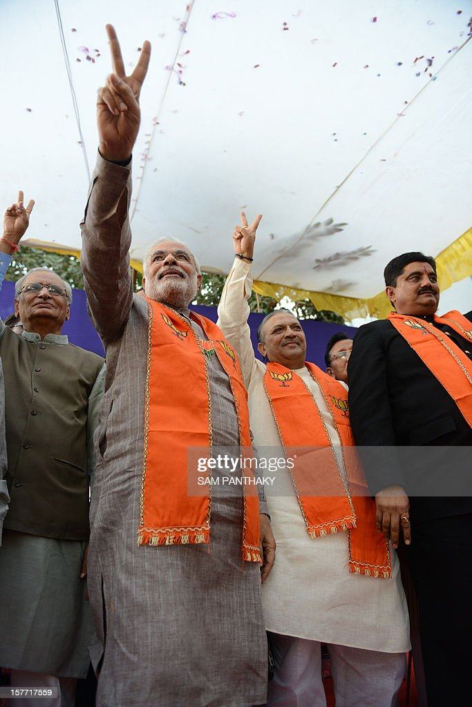 Indian senior Congress party leader and former Deputy Chief Minister of Gujarat state, Narhari Amin (2R), gestures after being inducted in the Bhartiya Janta Party (BJP) by the Gujarat state Chief Minister - Narendra Modi (2L) in Ahmedabad on December 6, 2012. Amin resigned from the Congress Party two days ago after he was denied a ticket to be on the Congress party ballot for the 2012 Assembly polls. AFP PHOTO / Sam PANTHAKY