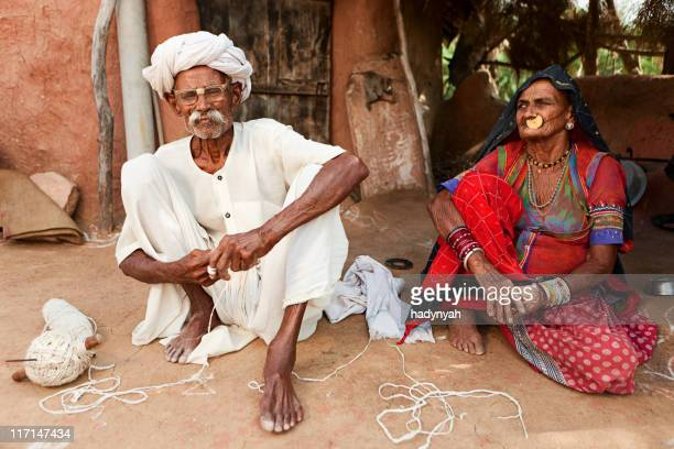Indian senior couple sitting inside clay hut. Bishnoi village. Rajasthan.