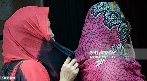 Indian sex workers with their faces covered watch a performance in the red light district of Kamathipura in Mumbai on August 28 ahead of the Hindu...
