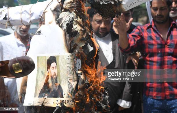 Indian Shiite Muslim demonstrators burn an effigy of the Islamic State group leader Abu Bakr alBaghdadi during a protest in New Delhi on June 9 2017...