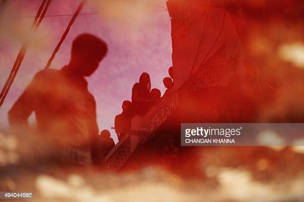 Indian Shiite Muslim devotees are reflected in a pool of blood left after others took part in ritual selfflagellation during an Ashura procession in...