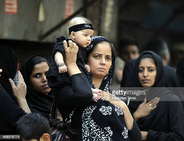 Indian Shiite Muslim woman with a child beats her chest as she mourns during a procession to mark Ashura on November 4 2014 in New Delhi India It is...