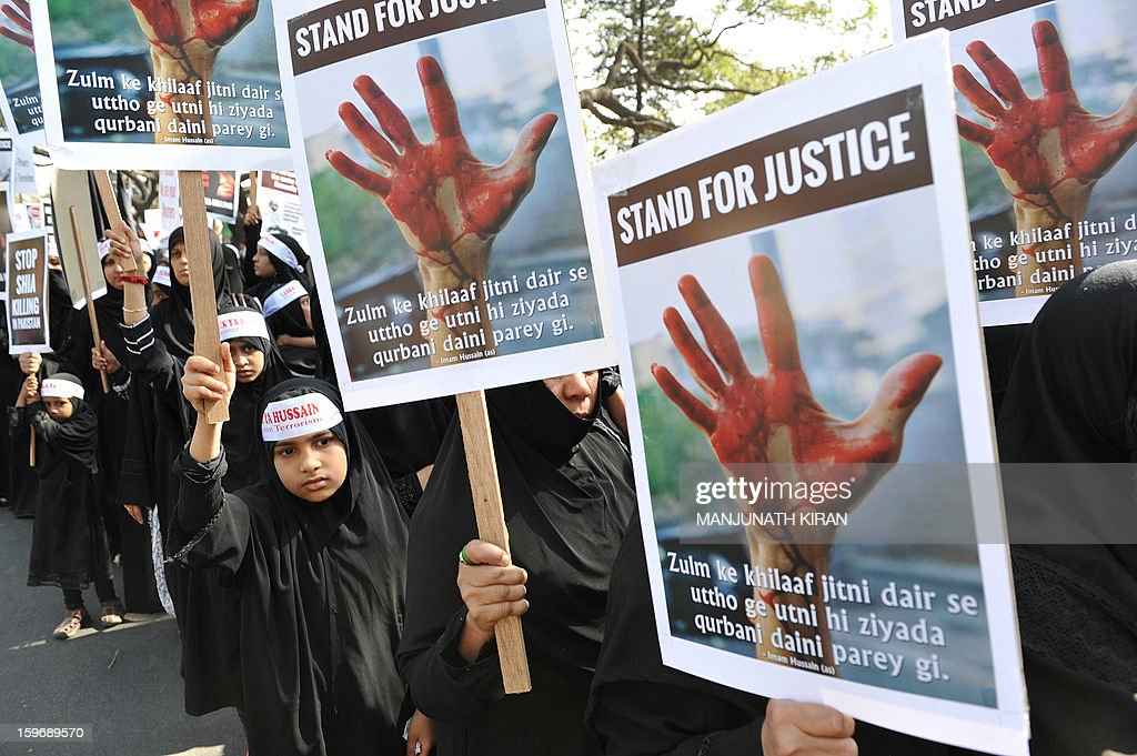 Indian Shiite Muslim women and children hold placards while taking part in a protest rally in Bangalore on January 18, 2013. The demonstrators were protesting against recent attacks against Shiite Muslims in Sunni-dominated Pakistan. AFP PHOTO/Manjunath KIRAN