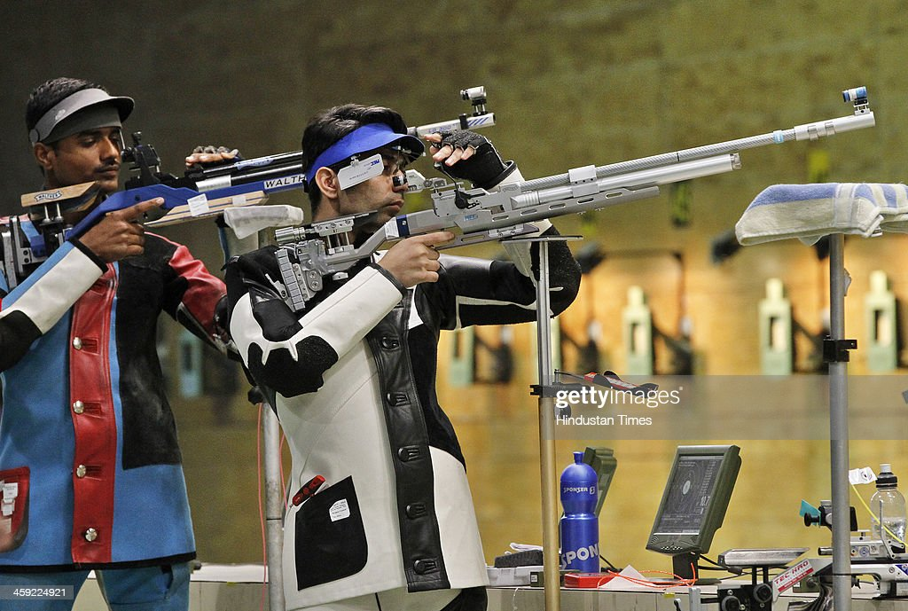 Indian shooter and Olympic gold medal winner <a gi-track='captionPersonalityLinkClicked' href=/galleries/search?phrase=Abhinav+Bindra&family=editorial&specificpeople=732431 ng-click='$event.stopPropagation()'>Abhinav Bindra</a> takes aim with rifle during 10-metre Air Rifle event's final round at National Shooting Championship, at Karni Singh Stadium on December 24, 2013 in New Delhi, India.