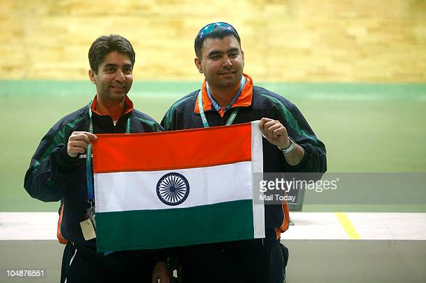 Indian shooters Abhinav Bindra and Gagan Narang holding the Tricolour after winning Gold in 10M Air Rifle Men event of Commonwealth Games at Dr K...