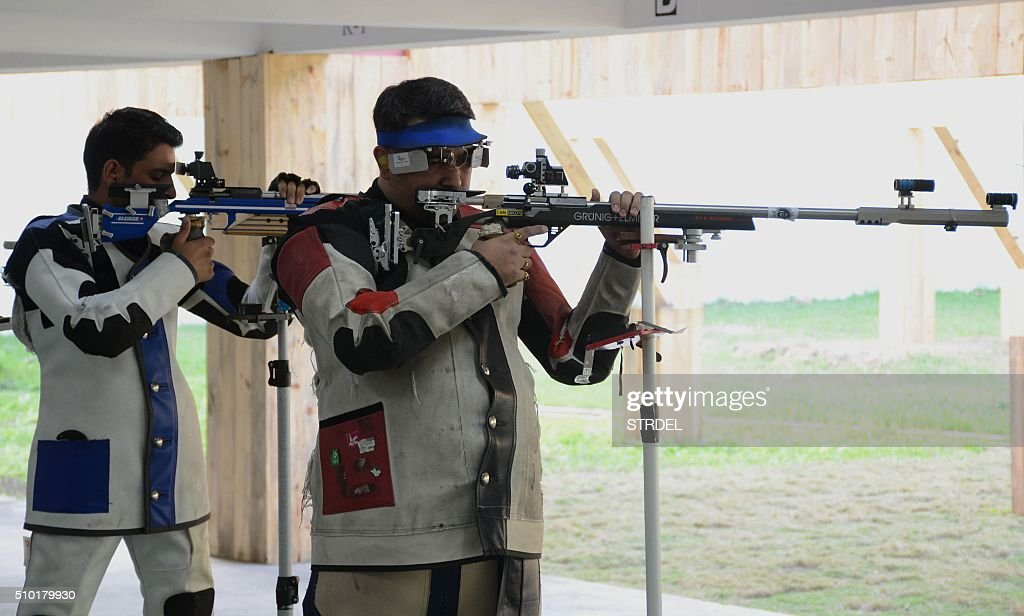 Indian shooting competitors Chain Singh (L) and Gagan Narang take part in the final of the Men's 50m individual rifle event at the 12th South Asian Games 2016 in Guwahati on February 14, 2016. Singh and Narang places first and second respectively. AFP PHOTO / Biju BORO / AFP / STRDEL
