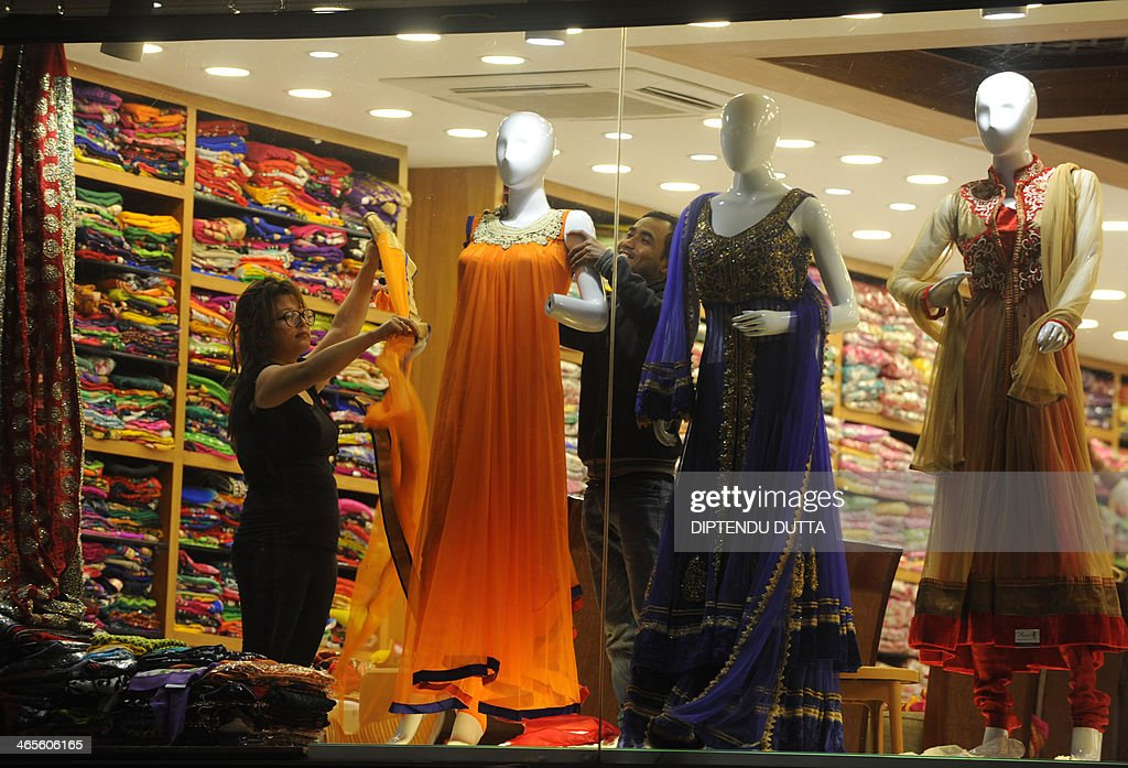 Indian shop employees adjust garments to mannequins displayed at a storefront in Siliguri on January 28, 2014. India's economy grew at a decade low of five percent in 2013 - a far cry from near-double digit expansion during the nation's boom times - due in part to high interest rates to combat inflation that have slowed borrowing and spending. AFP PHOTO /Diptendu DUTTA