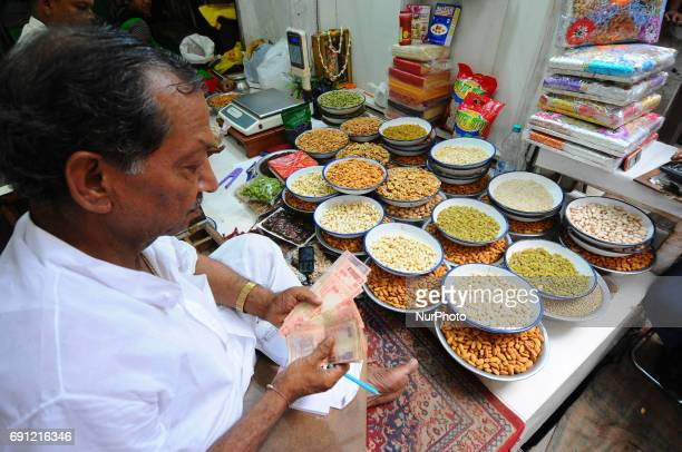 Indian shop keeper counting Indian Currency in the main wholesale market area of the city in KolkataIndia's economic growth slowed to 71 percent for...