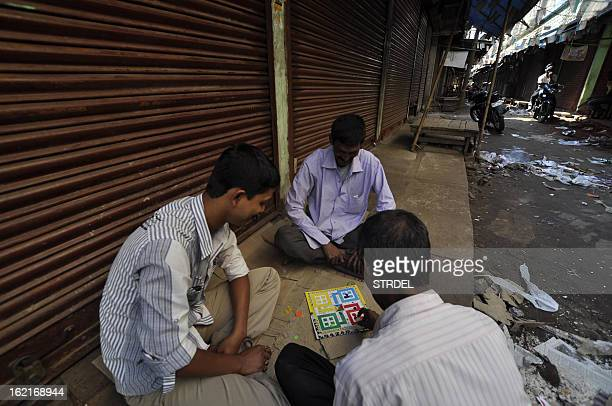 Indian shop owners play ludo inside of a closed wholesale market during a two day strike called by trade unions opposing the current UPA government's...