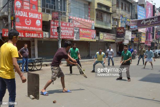 Indian shop workers play cricket next to closed clothes market stores shuttered during a protest against the central government's move to levy a...