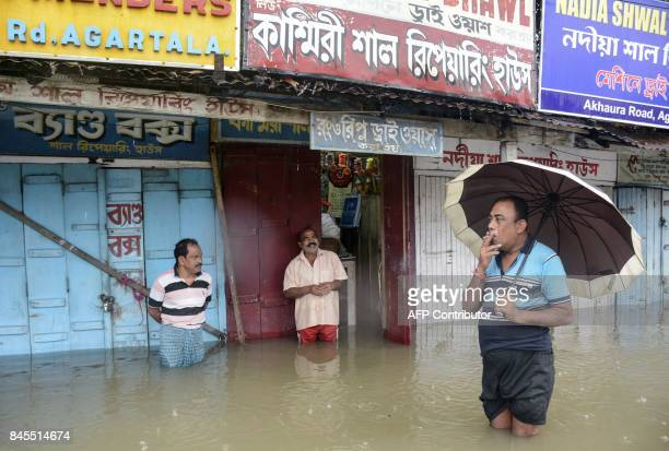 Indian shopkeepers stand on a flooded street next to their stores after a heavy downpour brought flooding to Agartala the capital of northeastern...