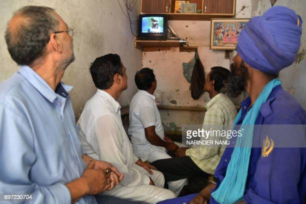 Indian shopkeepers watch the IndiaPakistan cricket final match taking place in London in Amritsar on June 18 2017 The Champions Trophy final match...