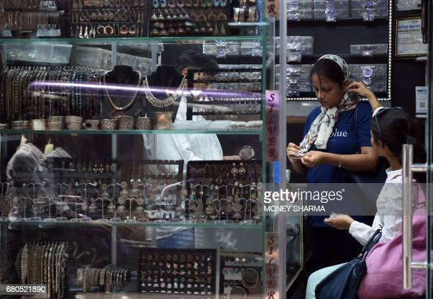 Indian shoppers look at jewellery in a shop in New Delhi on May 8 2017 Fat wads of bank notes move across counters in Old Delhi's gold and diamond...
