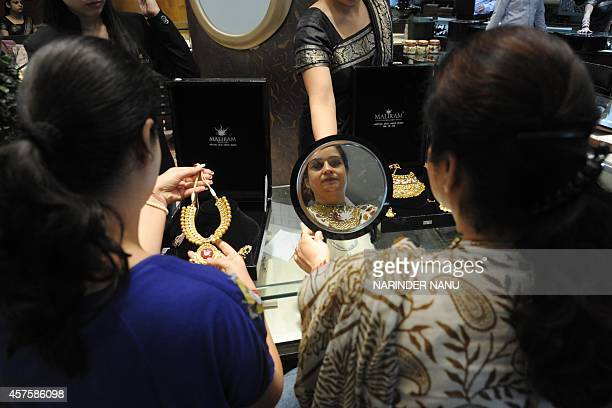Indian shoppers try on gold jewellery at a jewellery store on Dhanteras in Amritsar on October 21 2014 Dhanteras which happens two days before the...