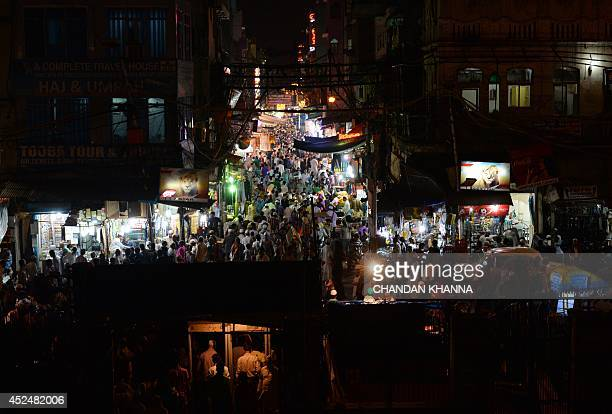 Indian shoppers walk through a market outside a mosque after the breaking of the Ramadan fast in New Delhi on July 21 2014 During the holy month of...