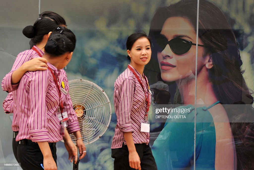 Indian shopping mall employees walk past a billboard in Siliguri on April 15, 2013. India's inflation unexpectedly slipped to below six percent for the first time in nearly three and half years, official data showed on Monday, fanning hopes of fresh interest rate cuts. AFP PHOTO/Diptendu DUTTA