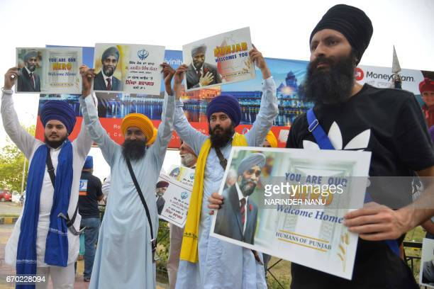 Indian Sikh activists pose with placards as they prepare for the arrival of Canada's Defence Minister Harjit Singh Sajjan at an airport on the...