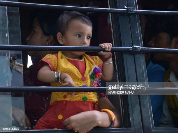 Indian Sikh child Hargun Kaur who was evacuated from flooding in Srinagar with family looks out from a bus window after their arrival at the airport...